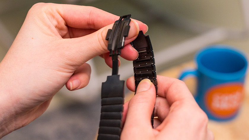 Hold down the release button on the inside of the strap.