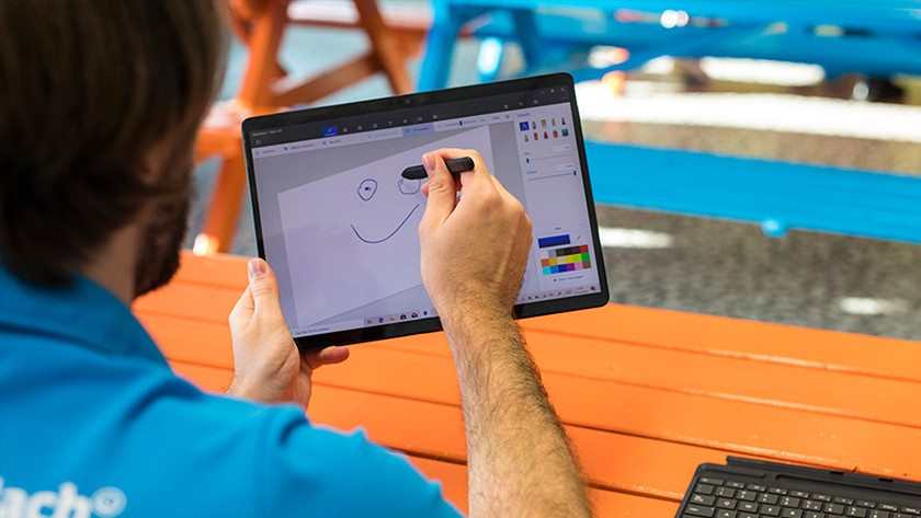 Man draws face on Surface laptop in tablet mode.