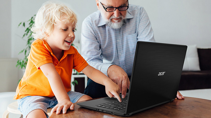 Grandfather and child work behind Acer laptop.