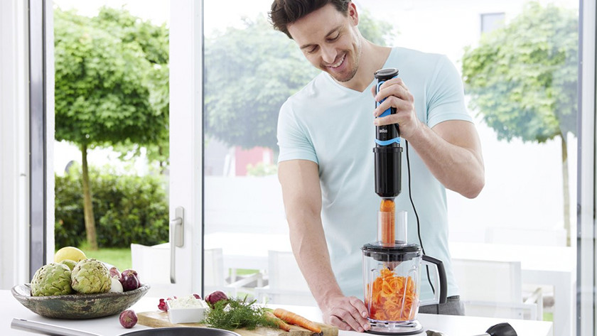 Man chops carrot with immersion blender and food processor attachment