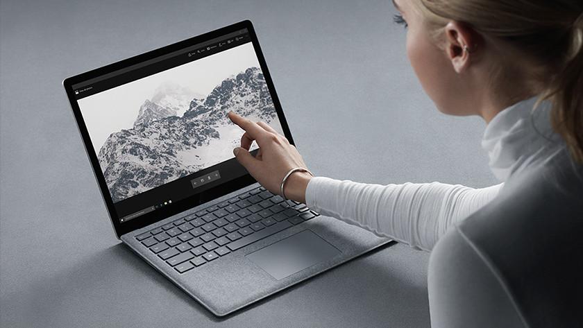 Vrouw tikt op touchscreen Surface Laptop.