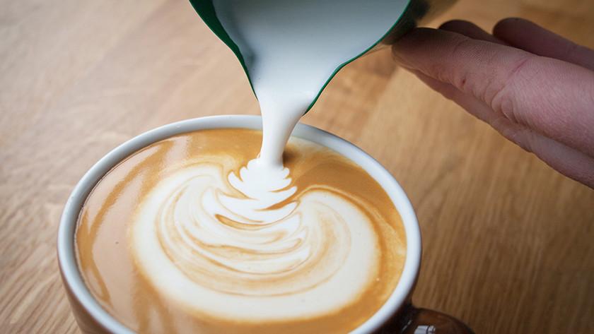Melk bij koffie gieten