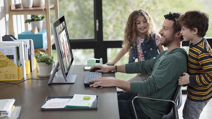 Man met twee kinderen zit aan bureau achter zijn all-in-one computer te werken.