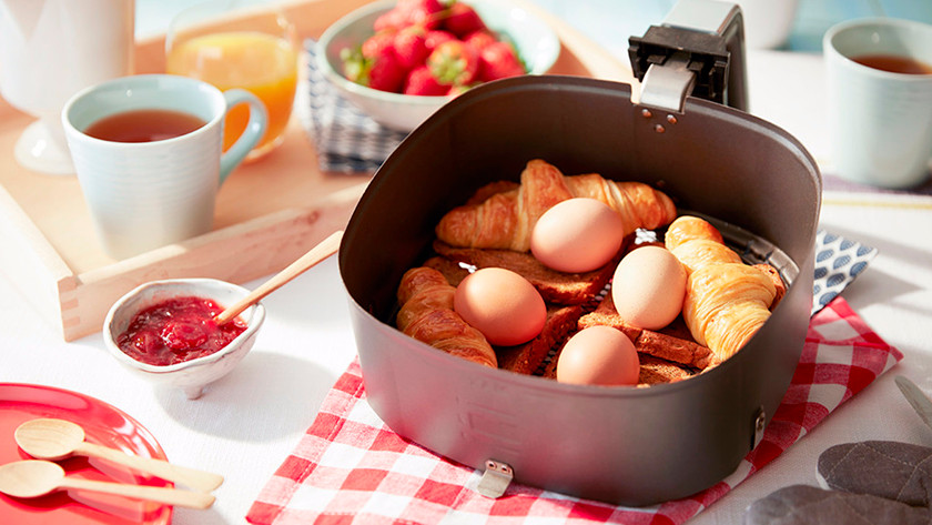 Airfryer basket with eggs and croissants