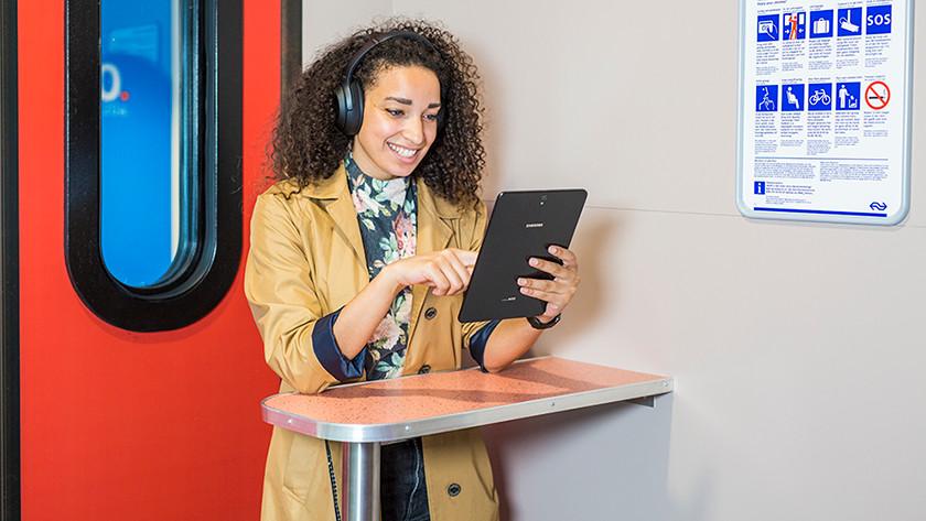 Blije vrouw werkt in trein op tablet.
