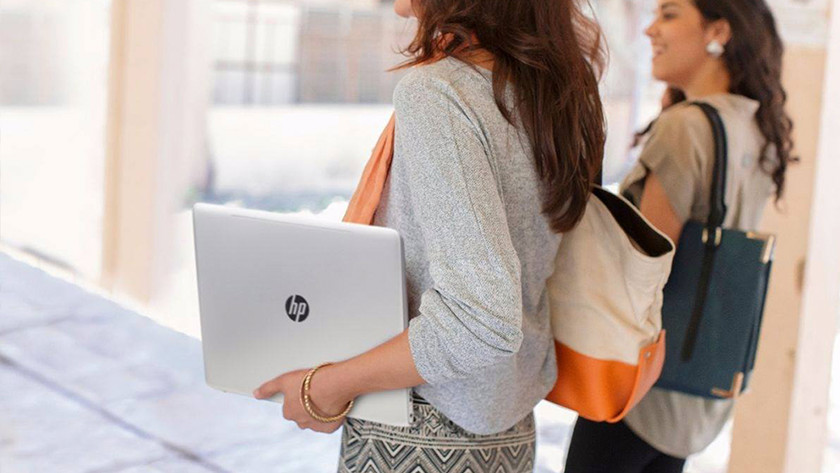 Woman walks through corridors with another woman with an HP laptop under arm.
