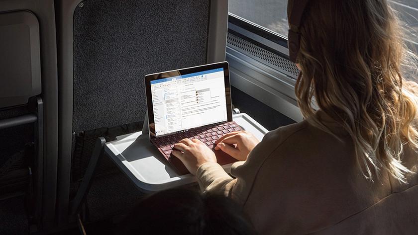 Vrouw werkt op Surface Go laptop in trein.