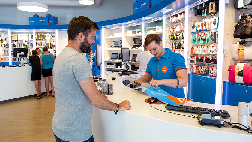 Coolblue medewerker doet laptop sleeve in plastic tas achter de balie in een Coolblue winkel.