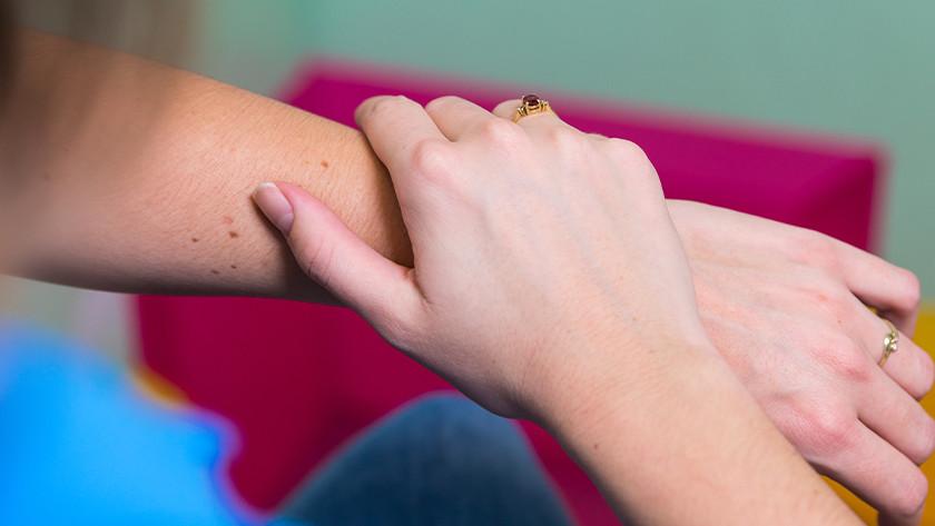 Leg nu je hand op het scherm van de Fitbit Sense en laat 'm erop rusten tot je een tikje op je pols voelt.