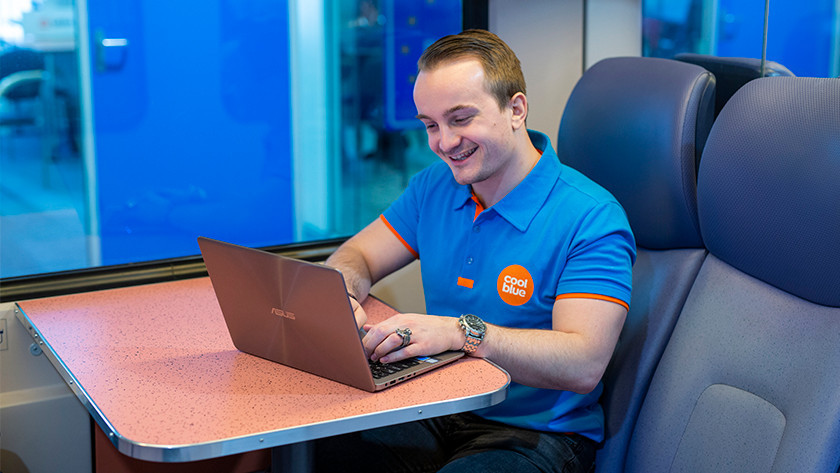 Blije man in trein werkt met Asus laptop.