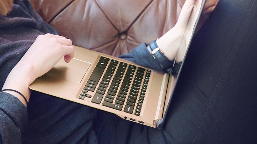 Woman uses Swift 7 on the couch for relaxation.