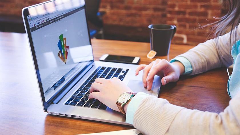 Vrouw bewerkt foto op laptop aan bureau.