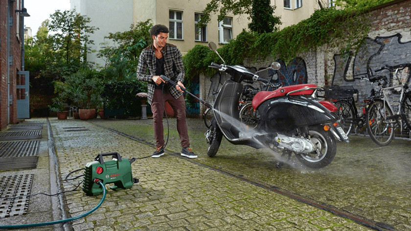 Spray cleaning a motorbike