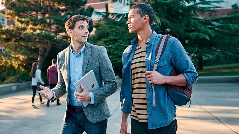 Man loopt buiten met Surface Pro onder arm en praat met andere man.