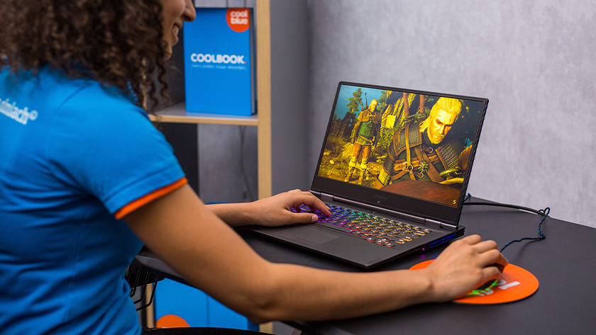 Woman playing Witcher on gaming laptop.