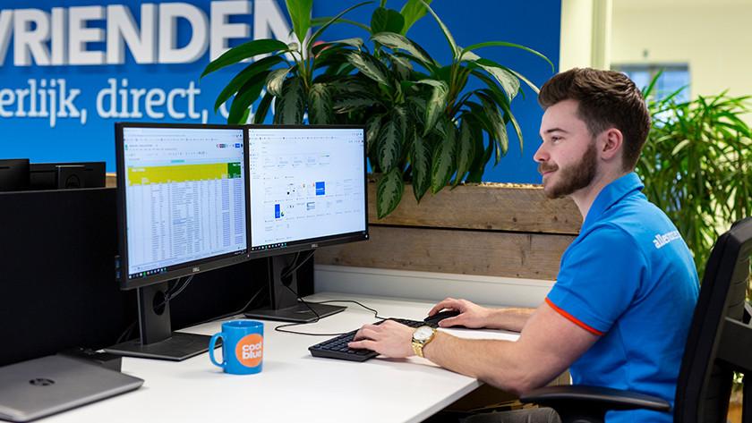 Coolblue medewerker werkt op kantoor achter bureau met twee monitoren erop.