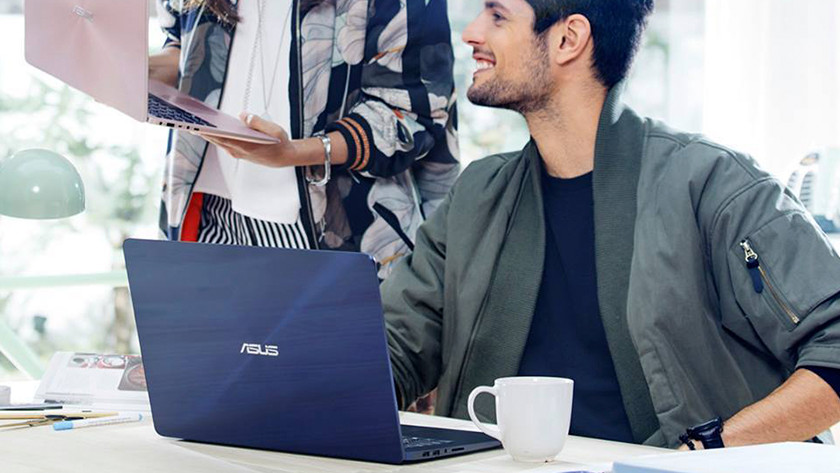 Man with Asus laptop behind desk looks at woman with Asus laptop.