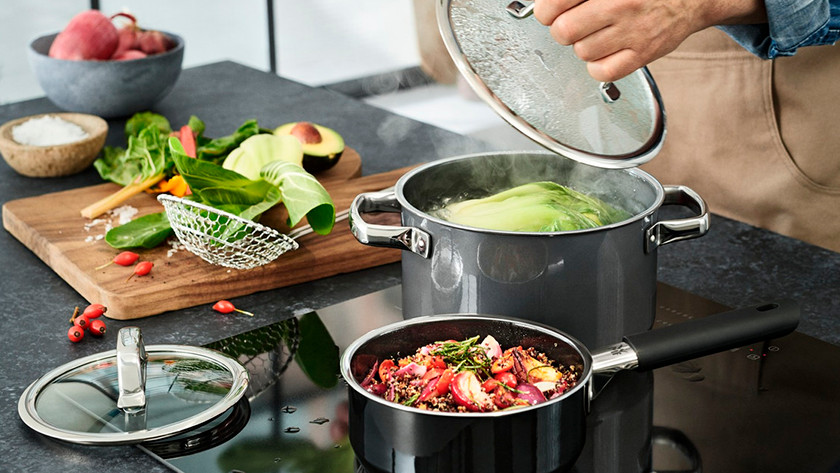 Saucepan and cooking pot with vegetables on stove