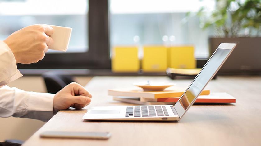 MacBook en hand met espresso mokje.