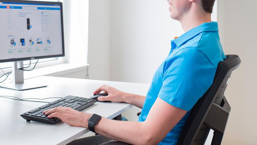 Man bekijkt in ergonomische houding achter bureau Coolblue website op beeldscherm.