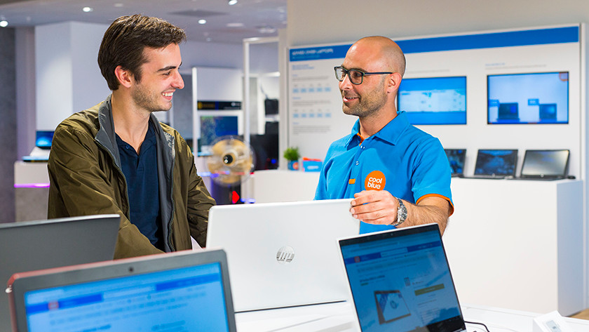 Coolblue employee showing HP laptop to customer in The Hague store.