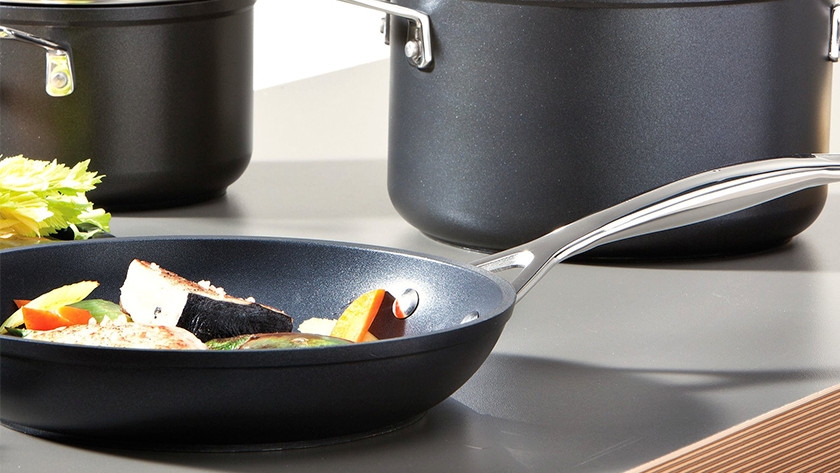 Frying pan with vegetables on kitchen counter