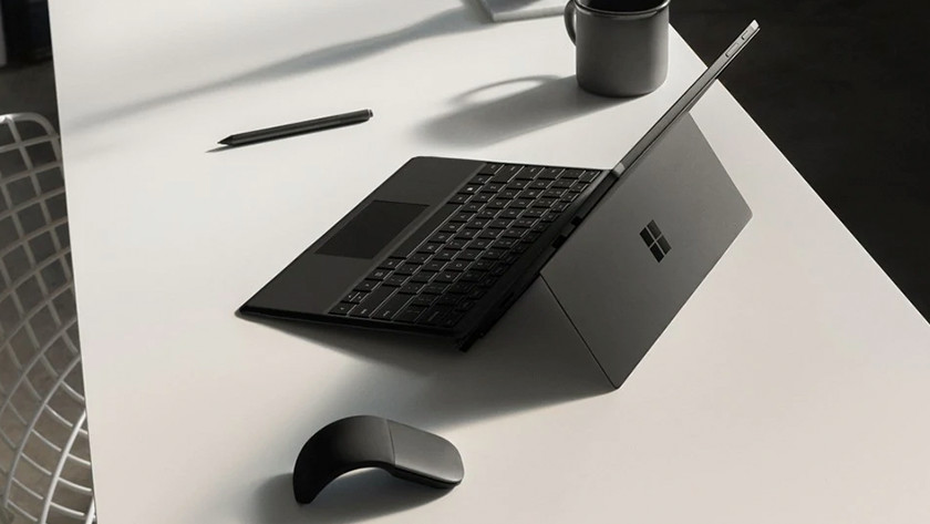 A 12-inch laptop on a desk with a mouse and pen next to it.