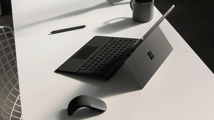 Een 12 inch laptop op een bureau met muis en pen ernaast.