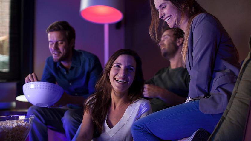 Mensen samen op bank met Philips Hue verlichting aan.