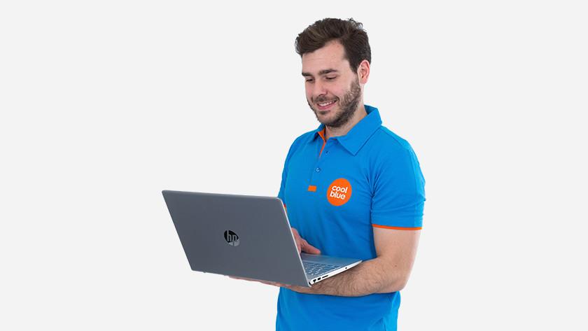 Blije man staat met laptop op arm.