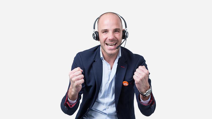Juichende zakenman met Coolblue badge op colbert. Op zijn hoofd een headset.