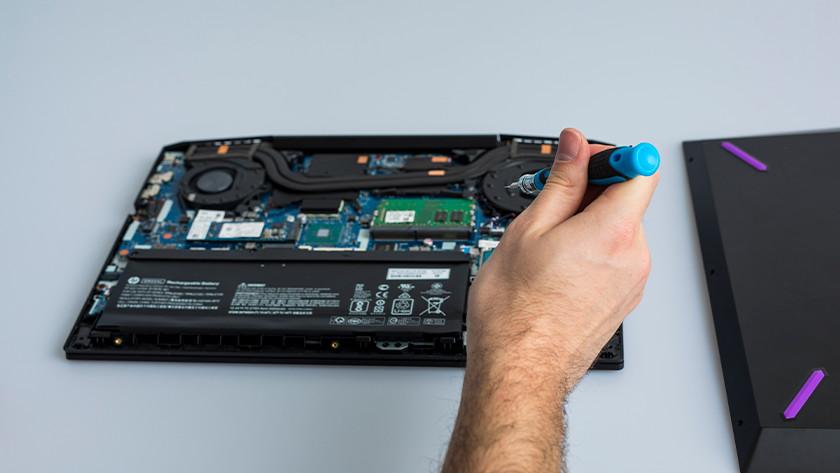 Hand beweegt schroevendraaier naar laptop.