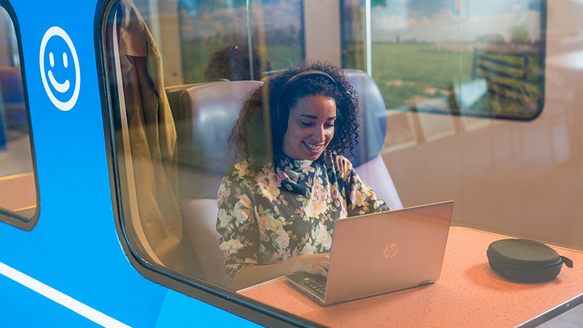 Meisje in trein werkt op HP laptop.