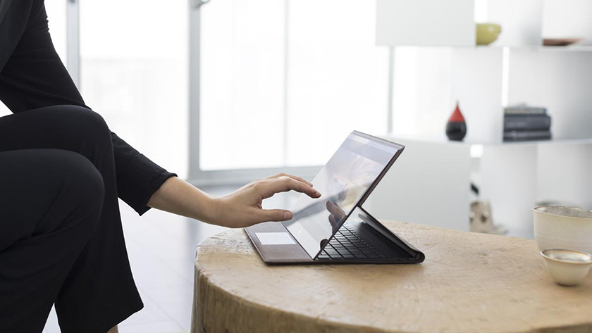 Woman's hand controls the HP Spectre Folio touchscreen.