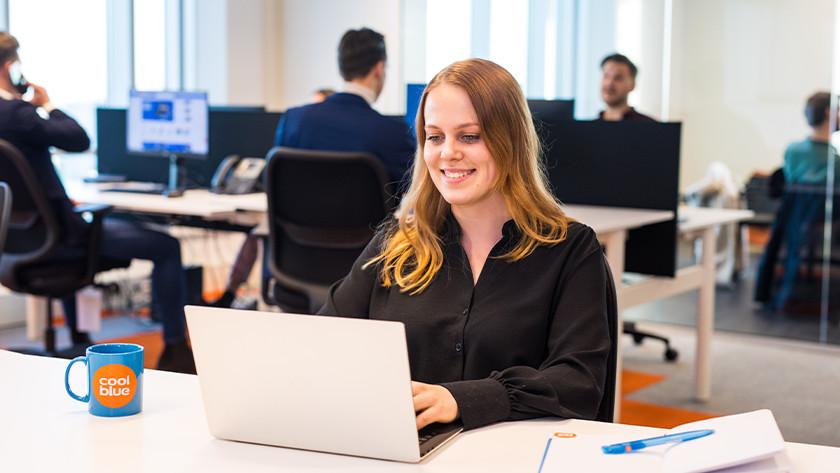 Meisje werkt op Coolblue kantoor achter zakelijke laptop.