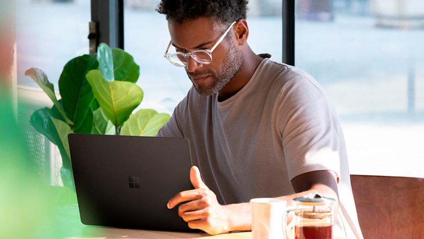 Man werkt op 13 inch laptop in koffiewinkel met plant op de achtergrond.