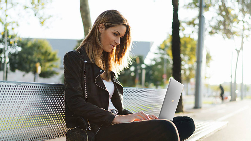 Woman works with laptop on lap on bus bench.