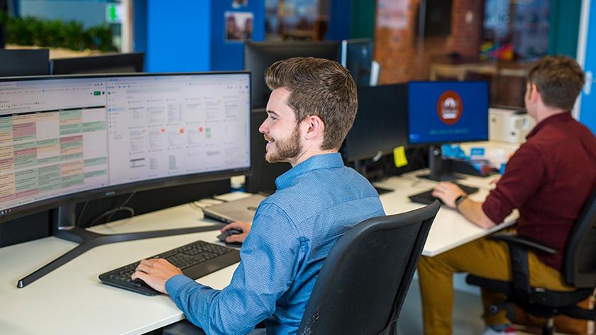 Man werkt achter monitor in kantoorruimte.