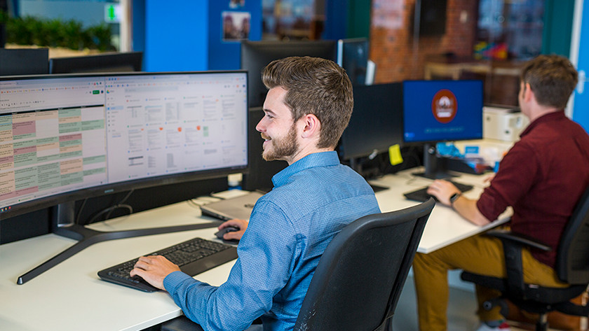 Man werkt op Coolblue kantoor achter monitor.