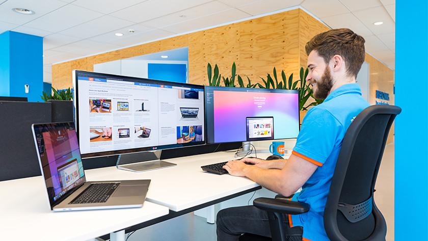 man werkt op 2 beeldschermen met macbook