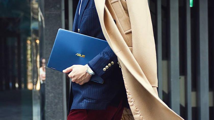 Zakenman met lange jas neemt Asus ZenBook mee onder zijn arm.