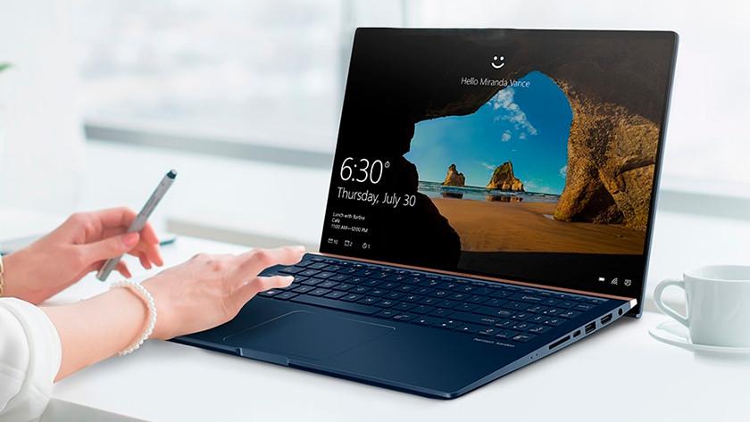 Vrouw werkt op 15 inch laptop met koffiekopje ernaast.