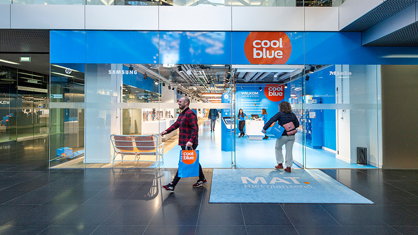 Man with Coolblue bag leaves Coolblue store after purchase.
