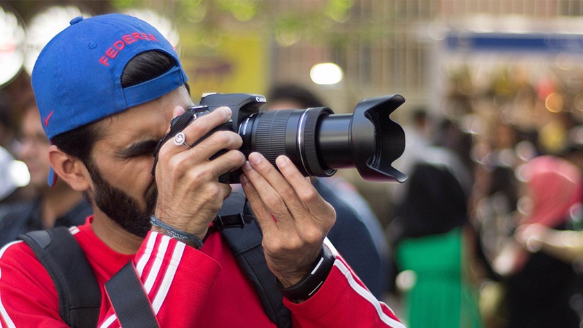 Man with red sweater and blue cap takes photo with camera.
