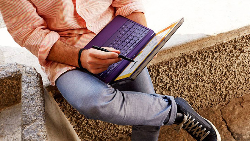Man works with pen on 2-in-1 business laptop.