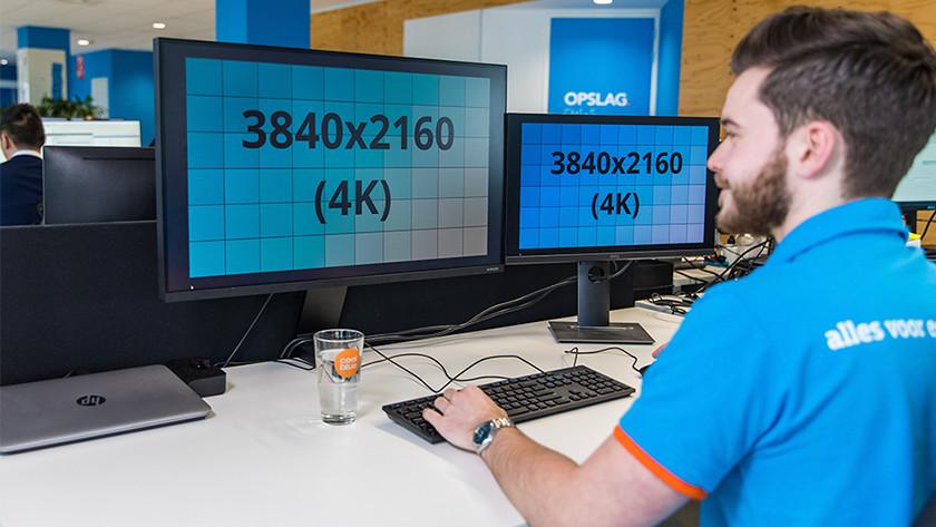 Man werkt aan bureau op scherm met 4K resolutie.\