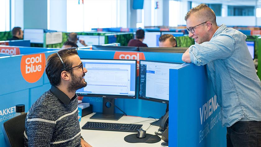 Man praat met Coolblue klantenservice medewerker op kantoor.