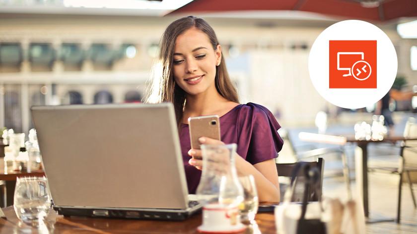 Vrouw op het terras bekijkt haar telefoon met een laptop voor zich op tafel. Een Remote Desktop logo in de rechter bovenhoek.