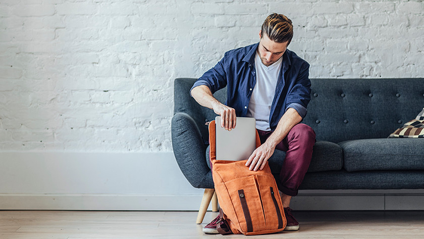 Man on couch puts laptop in orange backpack.