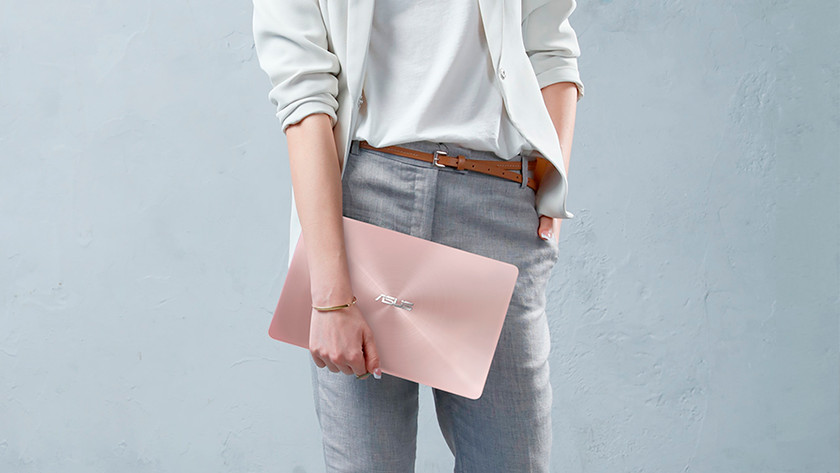 Woman holds 14-inch laptop with one hand, has the other on her hip.